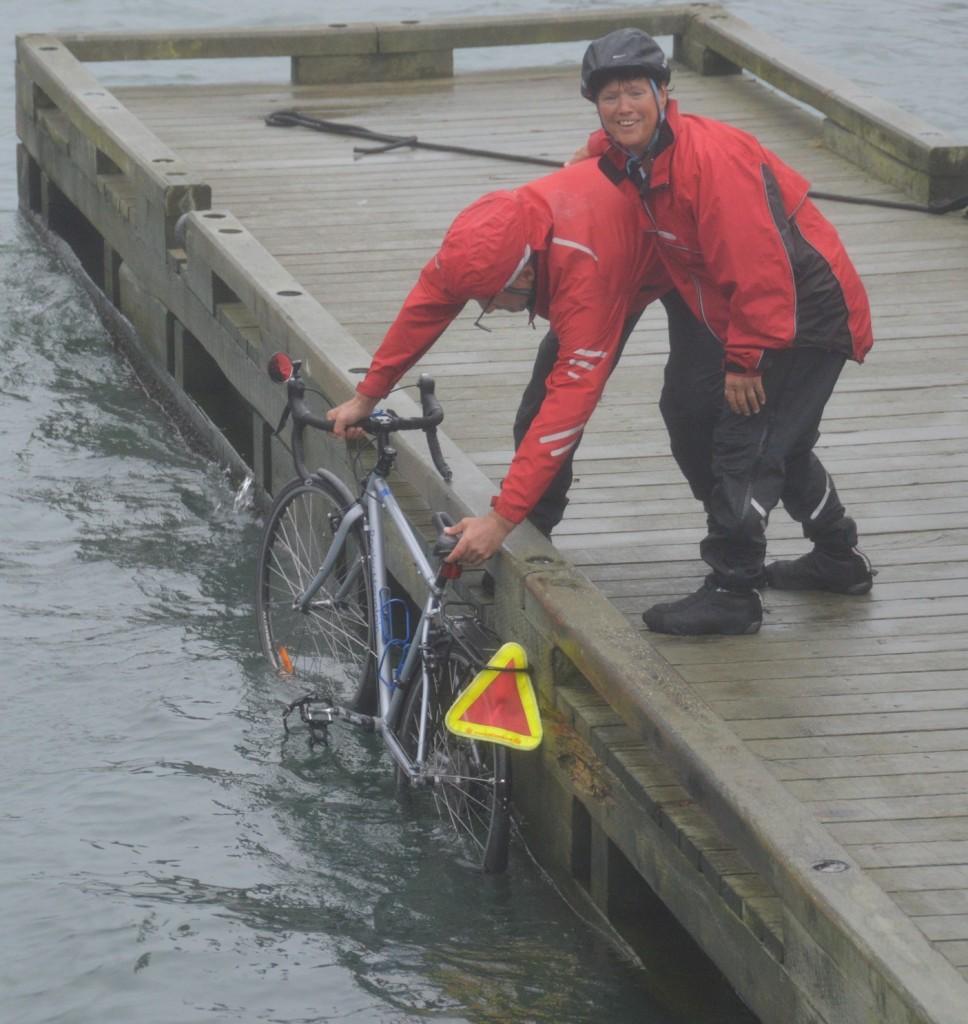 Joyce holding Clarke while he dips Joyces front wheel in Atlantic