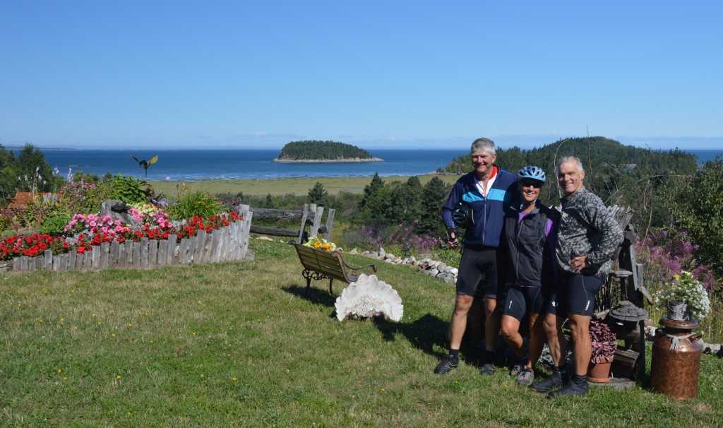 Mike, Joyce, and Dan posing in roadside garden along route #132 with St. Lawrence in background